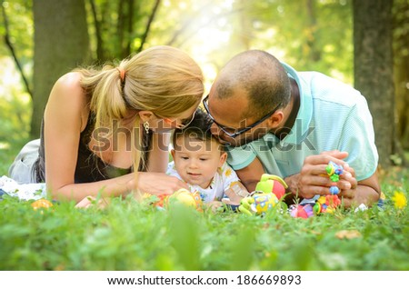 Happy interracial family is enjoying a day in the park - stock photo