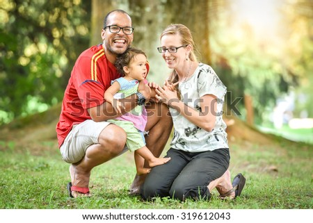 Happy interracial family is enjoying a day in the park. Little mulatto baby girl. Successful adoption. Diverse family in nature with sun in the back. - stock photo