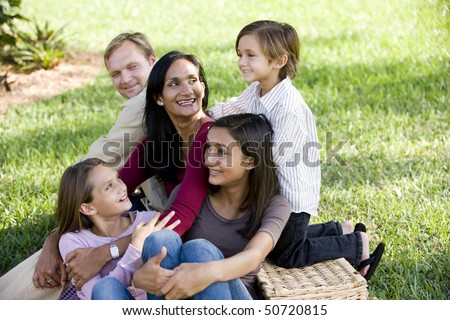 Happy interracial family with three children enjoying a picnic in the park - stock photo