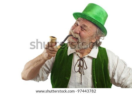 Happy Irish leprechaun with white beard, top hat, green velvet vest, and curved pipe in mouth. He raises eyebrows, smiles and tilts his head. Isolated on white, horizontal layout with copy space. - stock photo