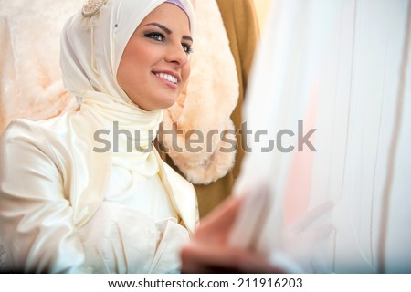 Happy islamic bride in white waiting by the window - stock photo