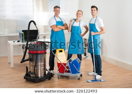 Happy Janitors With Vacuum Cleaner And Cleaning Equipments In Office - stock photo