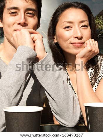 Happy Japanese couple sitting together at a coffee shop terrace having a hot coffee beverage and leaning on their hands while smiling at the camera during a sunny day, outdoors. - stock photo