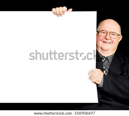 Happy jolly retired gentleman holding the side of a blank white sign or placard to advertise senior retirement and savings plans and offering his support and endorsement - stock photo