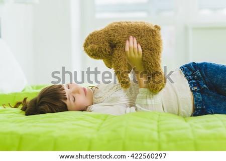 happy joyful and dreaming girl holding teddy bear indoor - stock photo