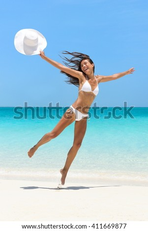 Happy joyful carefree girl jumping of joy on fun beach vacation getaway in tropical travel holiday destination. Happiness excitement, freedom, success in weight loss concept. Asian  bikini body woman. - stock photo