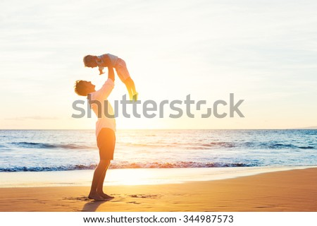 Happy Joyful Father and Son Having Fun Playing on the Beach at Sunset. Fatherhood Family Concept - stock photo