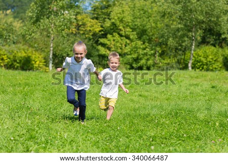 Happy joyful kids running on the grass in the autumn park - stock photo
