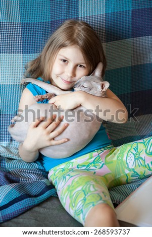 Happy joyful preschool age girl embracing sphynx cat on couch at home - stock photo