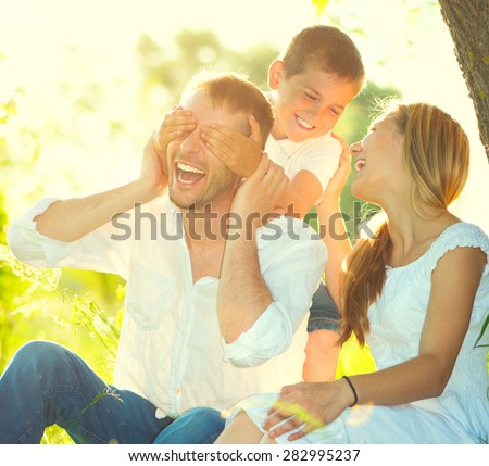 Happy joyful young family father, mother and little son having fun outdoors, playing together in summer park. Mom, Dad and kid laughing and hugging, enjoying nature outside. Sunny day, good mood - stock photo