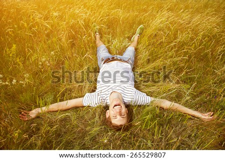 Happy joyful young man lying in the grass. summer outdoors. freedom, inspiration, success - stock photo