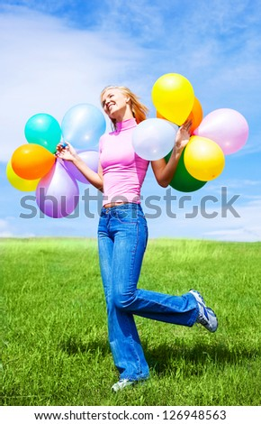 happy jumping young woman with balloons outdoor on a summer day - stock photo