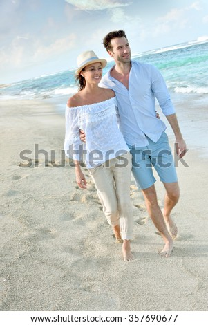 Happy just married couple walking on a sandy beach - stock photo
