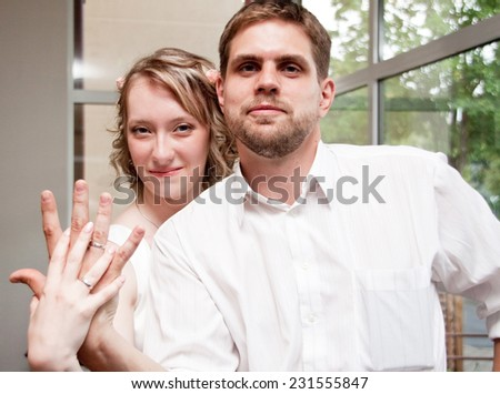 Happy just married man and woman show their wedding rings - stock photo