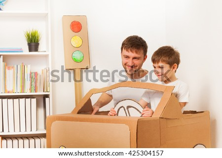 Happy kid and his dad driving toy cardboard car - stock photo