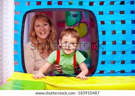 happy kid and nanny having fun on playground - stock photo