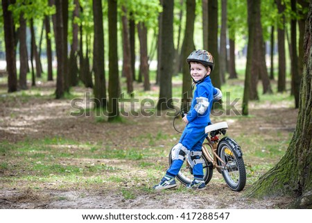 Happy kid boy of 4 years having fun in autumn forest with a bicycle on beautiful fall day. Active child making sports. Safety, sports, leisure with kids concept. - stock photo