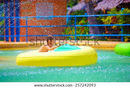 happy kid driving toy water boat in aqua park - stock photo