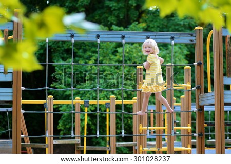 Happy kid enjoying active summer vacation. Adorable little child, blond cute toddler girl, having fun outdoors climbing on playground in the park on a sunny day. - stock photo