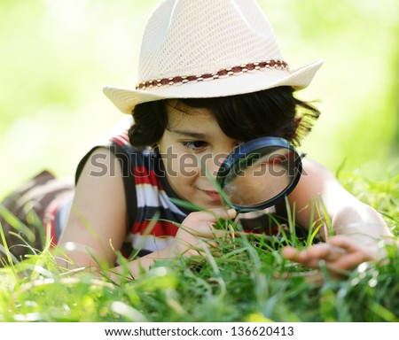 Happy kid exploring nature with magnifying glass - stock photo