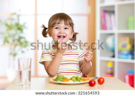 happy kid girl eating healthy food vegetables at home in nursery - stock photo