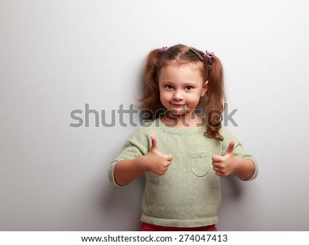 Happy kid girl showing thumb up of two hands on blue background with empty copy space - stock photo