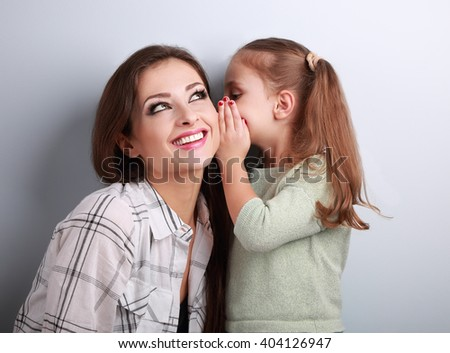 Happy kid girl whispering the secret to her smiling mother in ear with fun face on blue background - stock photo