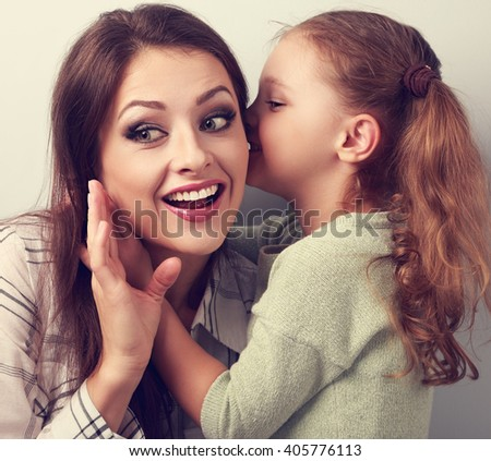 Happy kid girl whispering the secret to her surprising mother in ear with fun face. Toned closeup portrait - stock photo