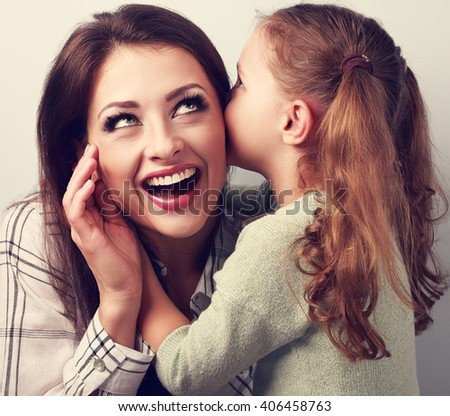 Happy kid girl whispering the secret to her very surprising mother in ear with fun face. Toned closeup portrait - stock photo