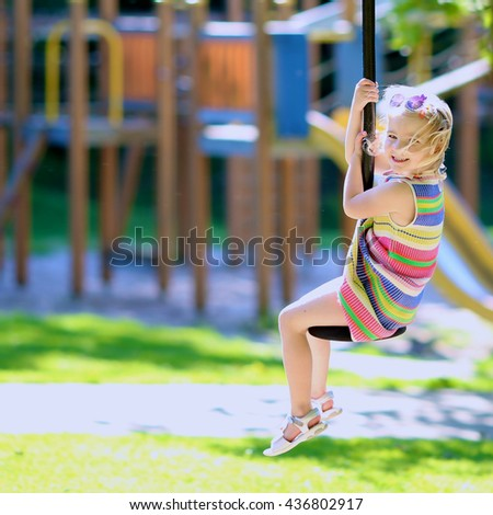 Happy kid having fun at playground. Adorable little child, blond cute toddler girl, enjoying active summer vacation outdoors playing in the park on a sunny day. - stock photo