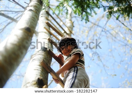 Happy kid having fun climbing on ladder in forest cabin - stock photo