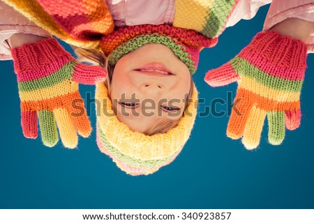 Happy kid having fun outdoors in winter against blue sky background - stock photo