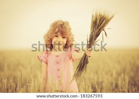 Happy kid holding wheat in summer field - stock photo