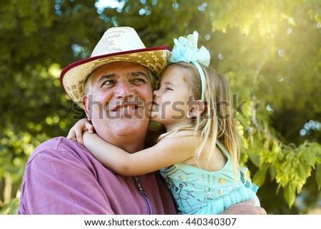 Happy kid hugging and kissing her grandfather in the park.  - stock photo
