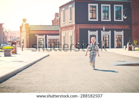 happy kid is running and laughing down the empty sunrise sunny street in the morning - stock photo
