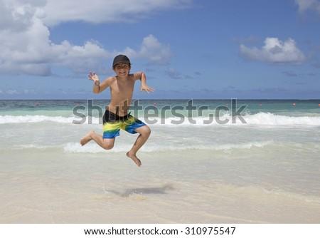 Happy kid jumping on a caribbean beach - stock photo