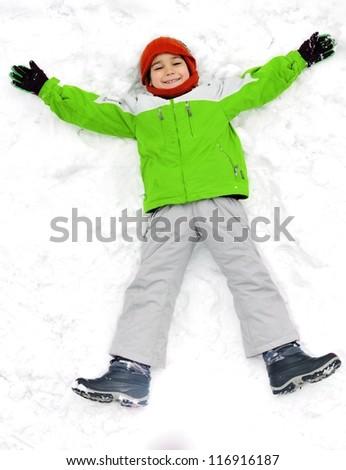 Happy kid lies on snow ground - stock photo