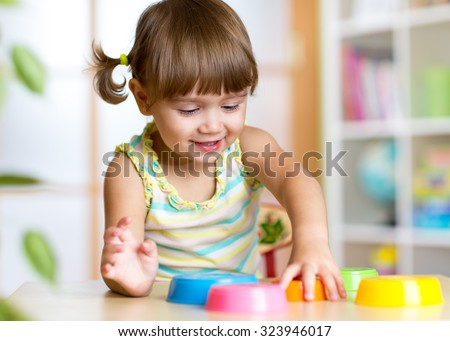 happy kid little girl playing with toys indoors - stock photo