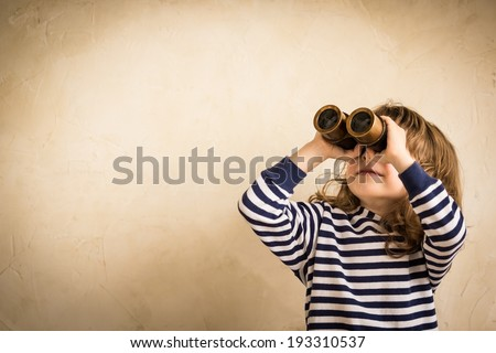 Happy kid looking ahead. Smiling child with spyglass. Travel and adventure concept. Freedom, vacation - stock photo