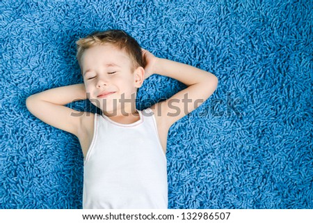 Happy kid on floor in living room at home - stock photo