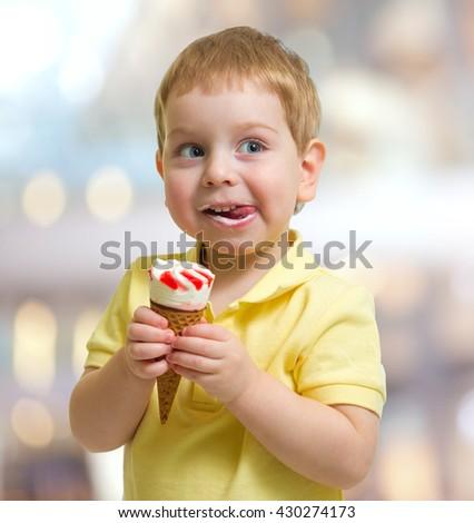 Happy kid or child eating icecream - stock photo