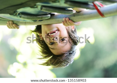 Happy kid outdoors in nature having good time hanging upside down - stock photo