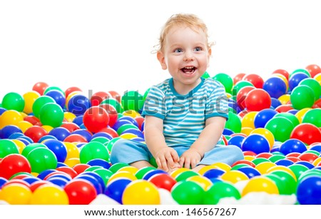Happy kid playing colorful balls - stock photo