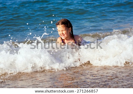 Happy kid playing playing on beach in the sea waves - stock photo