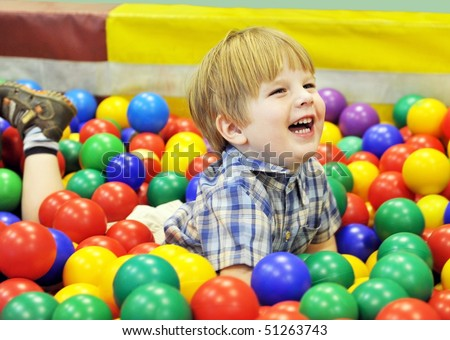 happy  kid playing with colored balls - stock photo