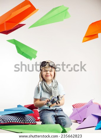 Happy kid playing with paper airplane - stock photo