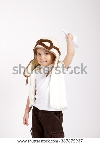 happy kid playing with paper airplane. studio photo. aviator hat and scarf - stock photo
