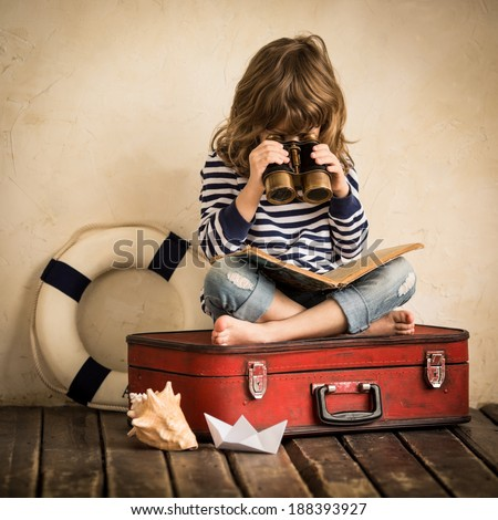 Happy kid playing with toy sailing boat indoors. Child with spyglass reading book. Travel and adventure concept - stock photo