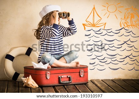 Happy kid playing with toy sailing boat indoors. Travel and adventure concept - stock photo