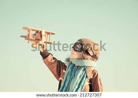 Happy kid playing with toy wooden airplane against autumn sky background. Retro toned - stock photo